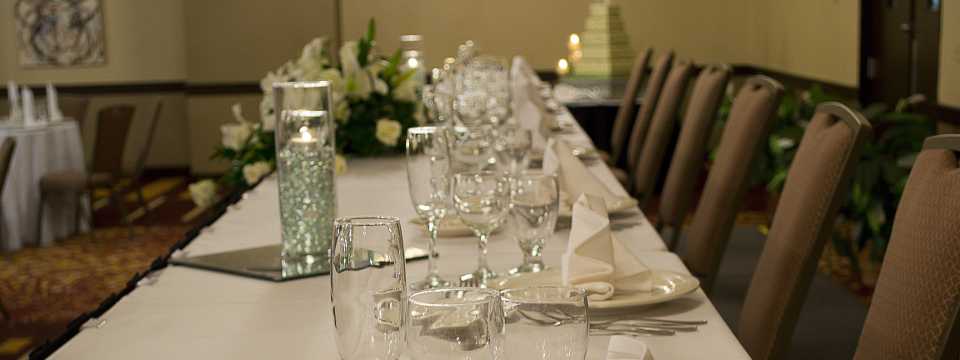 Hotel's ballroom set up for formal event with glassware