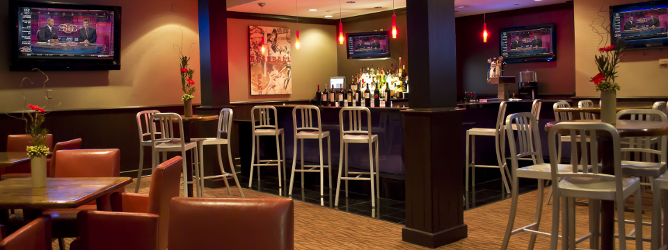 Well-stocked sports bar with TVs, tables and bar seating
