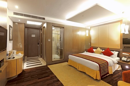 Hotel room with bed, wood floors and glass shower