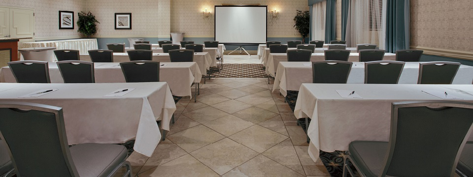 Hotel meeting room with a classroom setup and a projector screen