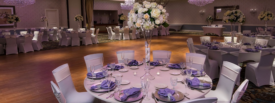 Elegant ballroom with a banquet setup and lavender accents