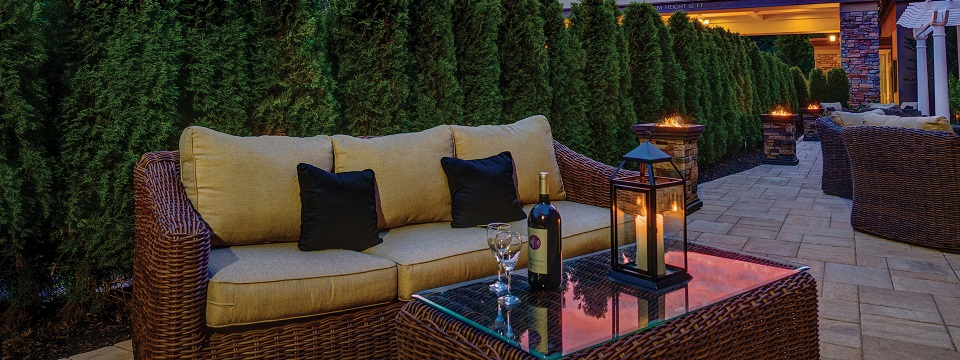 Outdoor patio with wicker furniture, wine and greenery