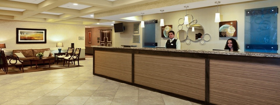 Hotel lobby featuring a front desk and a comfortable seating area
