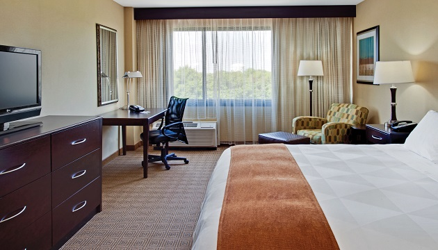 Freehold hotel room featuring a bed with crisp white linens and a work desk