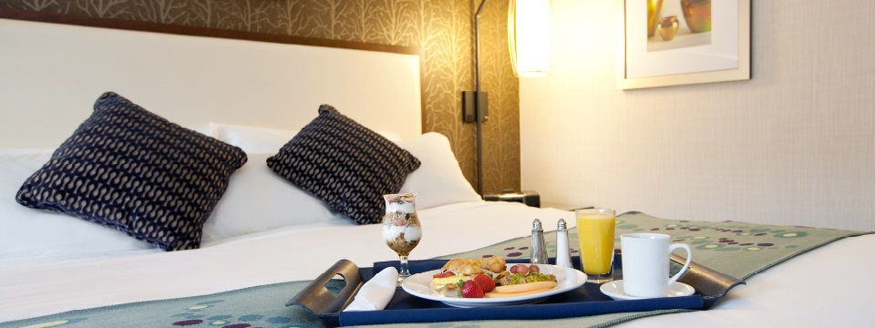 Guest room with tray of yogurt, orange juice and fruit