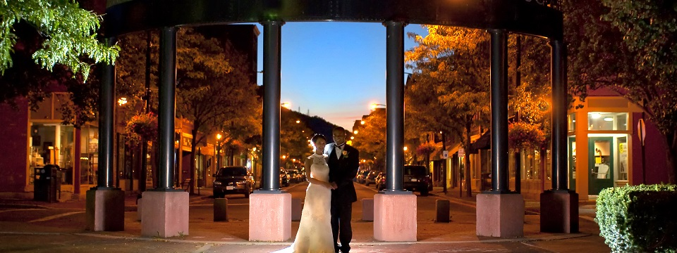 Bride and groom standing in downtown Corning at night