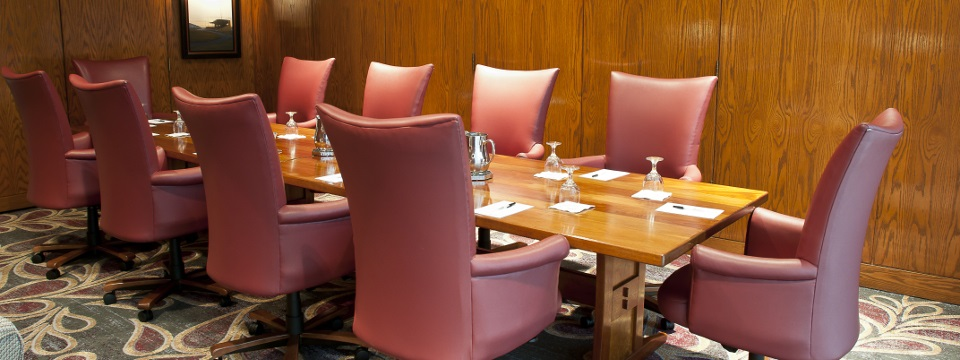 Boardroom with long wooden table surrounded by red chairs