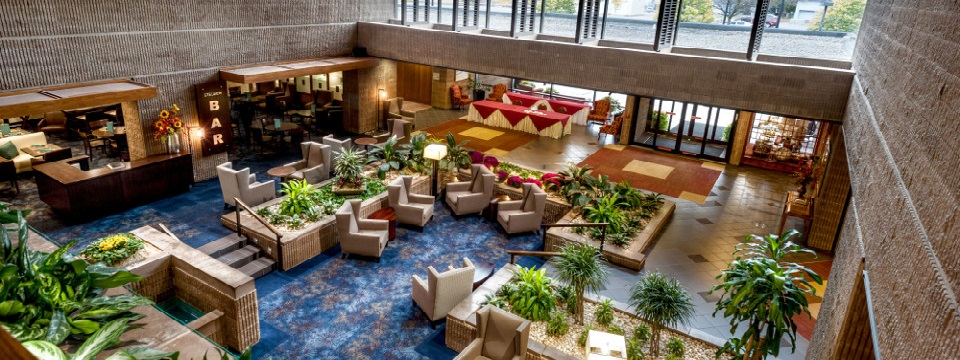 Spacious lobby with colorful rugs, greenery and ample seating