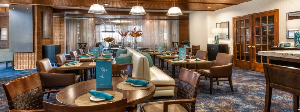 Dining area with tables, chairs and teal accents