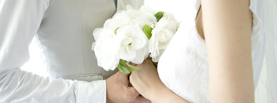 Bride and groom holding a white bouquet