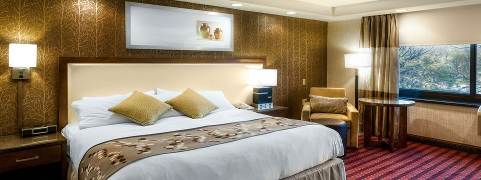 Spacious suite with king bed, armchair and ample lighting