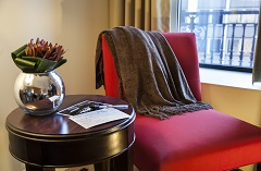 Red chair with a brown blanket draped over the back