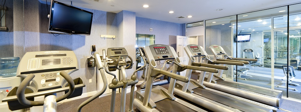Fitness center with three treadmills, an elliptical and a flat-screen TV
