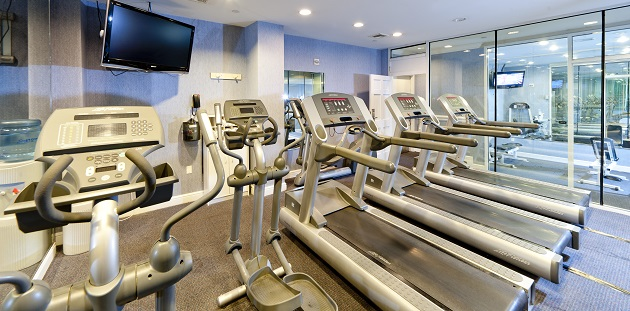 Hotel's fitness center with three treadmills, an elliptical and a flat-screen TV