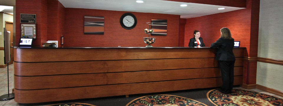 Front desk staff welcoming a guest in the lobby