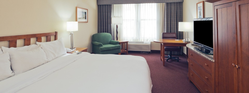 Cleveland hotel room with a king bed and a green armchair