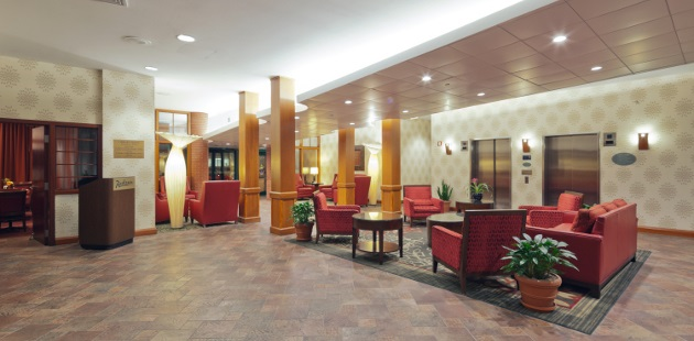 Spacious lobby with red seating and greenery