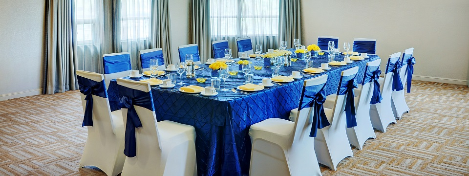 Table and chairs decorated with blue decor and yellow flowers