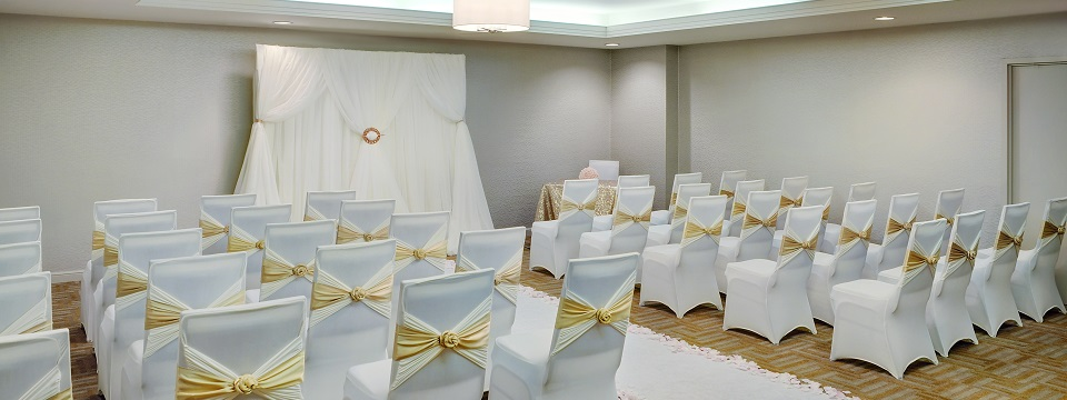 Chairs decorated with a white and gold theme for a wedding