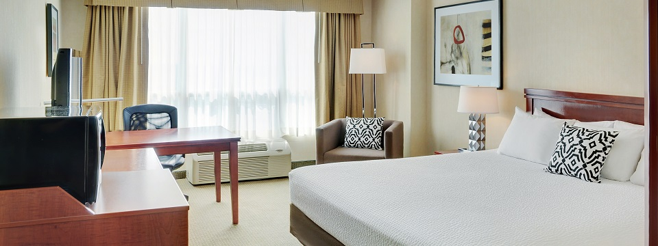Hotel room with a king bed, desk and armchair