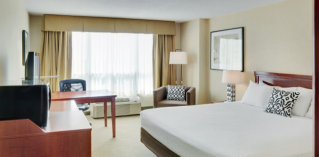 Hotel room with a king bed, work desk and armchair