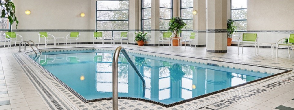 Indoor pool surrounded by chairs and plants