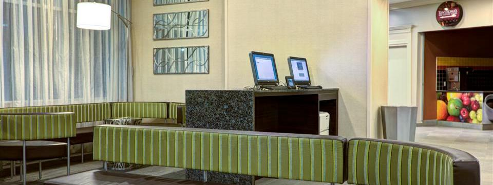 Modern business centre with two computers, a printer and seating