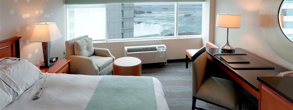 Guest room with king bed and armchair overlooking Niagara Falls