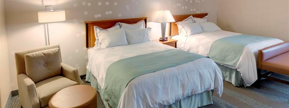 Two queen beds with teal accents and an armchair in hotel room