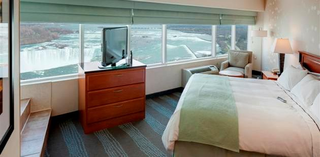 Guest room with king bed, flat-screen TV and view of Niagara Falls