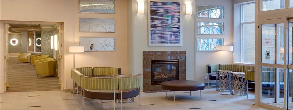Contemporary seating and decor in spacious hotel lobby with a fireplace