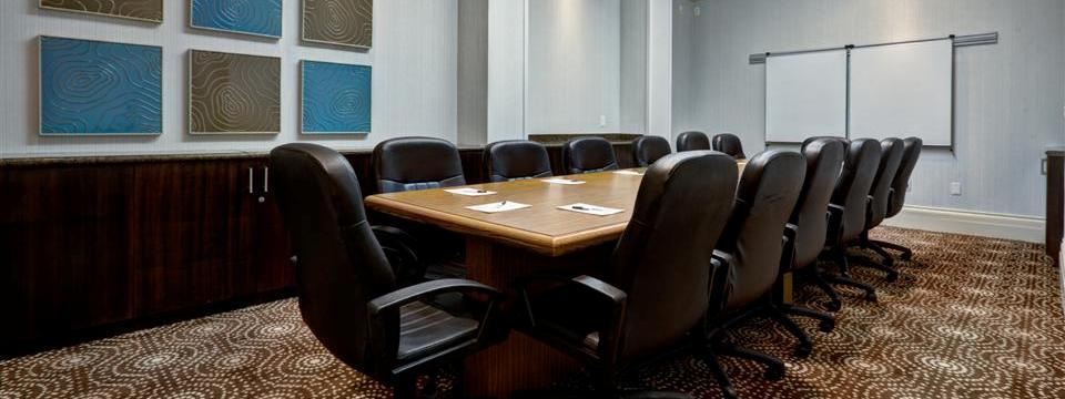 Boardroom with conference table, leather chairs and projection screens