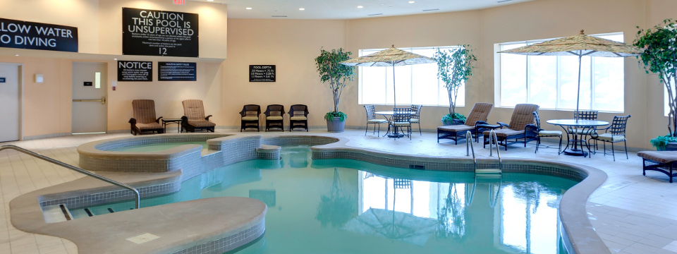 Organically shaped indoor pool surrounded by lounge chairs