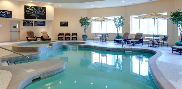 Sparkling indoor pool surrounded by lounge chairs