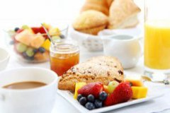 Breakfast spread with fruit, pastries, coffee and orange juice