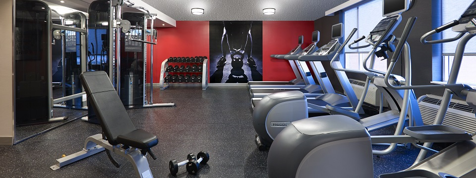 Fitness centre with treadmills, ellipticals, weights and red wall