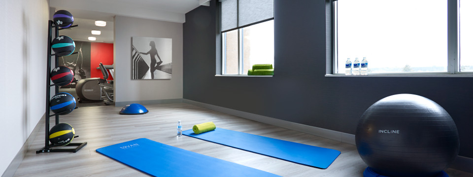 Yoga balls and mats in brightly lit hotel fitness facility