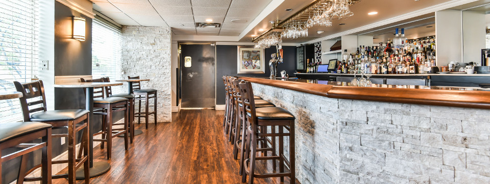 Stools at well-stocked, stone-accented bar in Toronto hotel