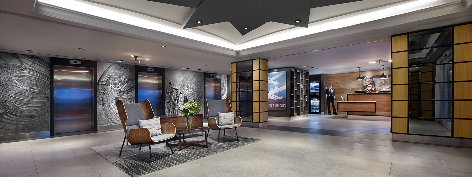 Hotel lobby with grey abstract art, chairs and elevators
