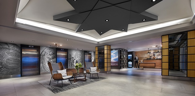 Lobby with chairs and modern wall art between elevators