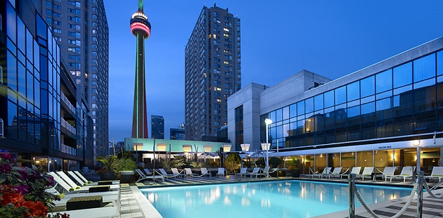 Outdoor pool with city views lit up at night