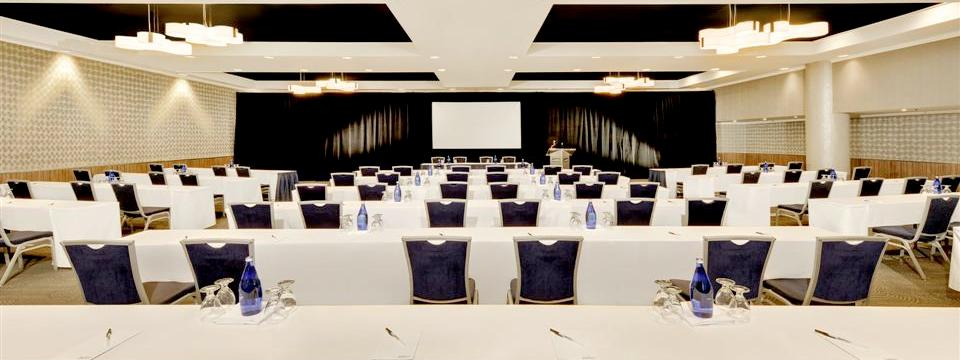 Rows of tables and chairs facing a white projection screen