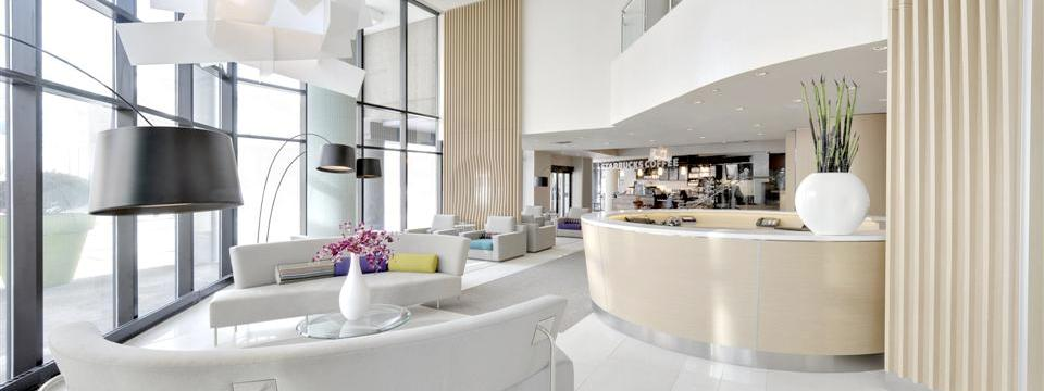 Elegant hotel lobby with white furniture and colourful pillows