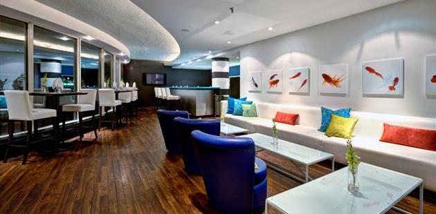 Watermark Lounge with white chairs and colorful pillows