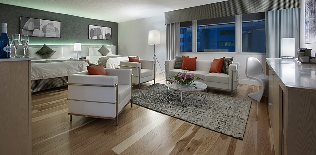 Studio Room with two beds and white chairs with orange accents