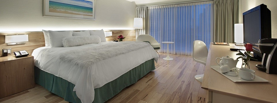 Hotel guest room with white bedding and wood floors