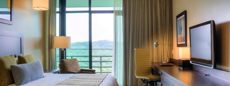 Suite with king bed, armchair and balcony overlooking greenery