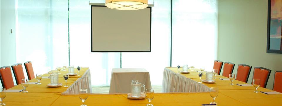 U-shaped table and chairs facing projector screen in event space