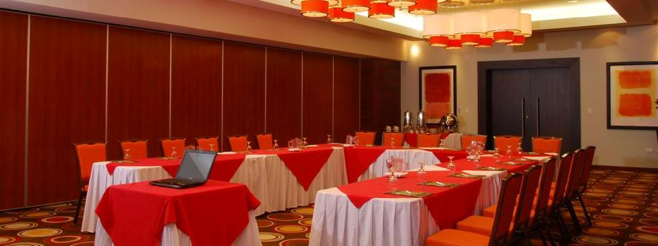 U-shaped table in meeting space with glassware and red linens