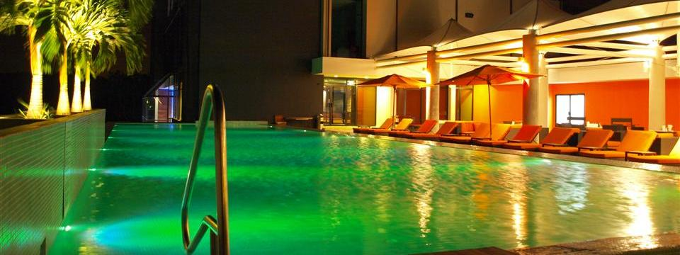 Outdoor pool at night surrounded by lounge chairs
